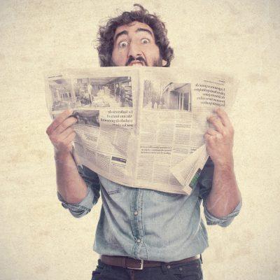 man looking over newspaper headlines